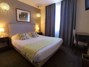 A bed or beds in a room at Brit Hotel Acacias