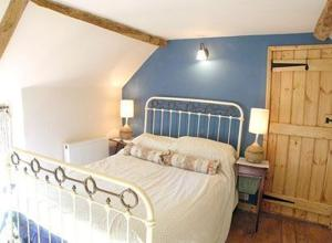 A bed or beds in a room at Brook Cottage