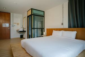 A bed or beds in a room at Karpenter Lampang