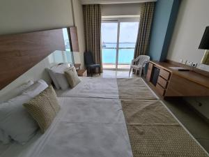 A bed or beds in a room at Water's Edge Hotel
