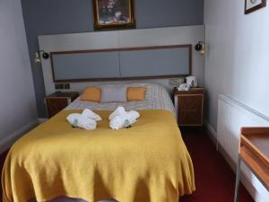 A bed or beds in a room at The Royal Oak Hotel
