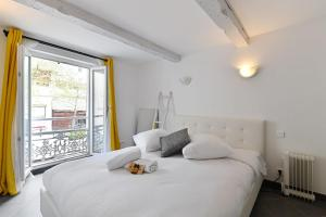 A bed or beds in a room at Charming flat overlooking the Place de Lenche in Marseille - Welkeys