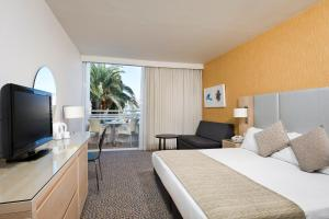 A bed or beds in a room at Isrotel Lagoona All-Inclusive Hotel