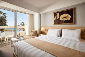A bed or beds in a room at Tylissos Beach Hotel