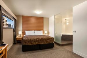 A bed or beds in a room at The Old Woolstore Apartment Hotel