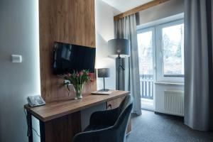 A television and/or entertainment center at Nowa - Ski SPA Hotel