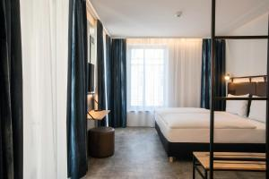 A bed or beds in a room at H2 Hotel Budapest