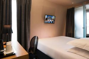 A bed or beds in a room at Best Western Plus Quartier Latin Pantheon