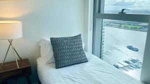 A bed or beds in a room at Modern Docklands Apartment City View 3B LV34