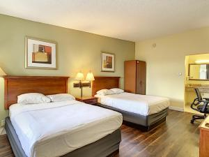A bed or beds in a room at Stayable Suites Florida Mall Orlando