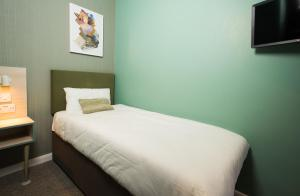 A bed or beds in a room at Caring Hotel