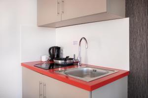 A kitchen or kitchenette at KU Hotel