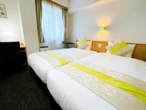 A bed or beds in a room at Eins.Inn Umeda Higashi