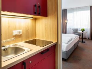 A kitchen or kitchenette at Plaza Hotel & Living Frankfurt
