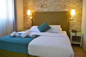 A bed or beds in a room at Kalia Kibbutz Hotel