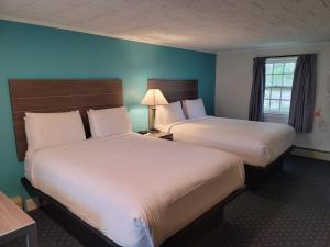 A bed or beds in a room at Olde Tavern Motel and Inn
