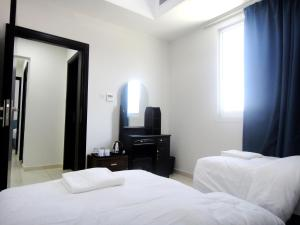 A bed or beds in a room at Al Badaa Star Residence