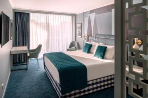 A bed or beds in a room at Juliana Hotel Cannes
