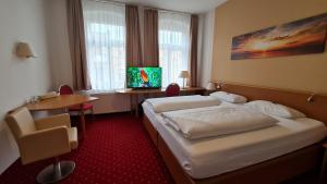 A bed or beds in a room at City-Hotel Am Wasserturm Halle