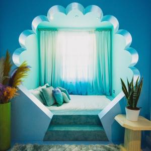 """A bed or beds in a room at Unique & fun coastal getaway, 1 minute walk to the beach - pastel interiors created by local artists in a Town centre location """"The Courtyard Suite"""""""
