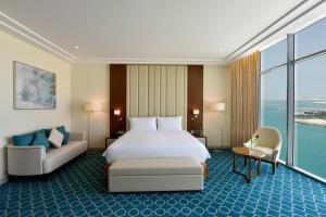 A bed or beds in a room at Grand Swiss-Belhotel Waterfront Seef