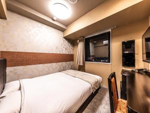 A bed or beds in a room at APA Hotel Shin Osaka-Eki Tower
