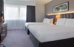 A bed or beds in a room at DoubleTree by Hilton Edinburgh Airport