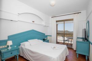 A bed or beds in a room at Hotel y Bungalows Balcón de Competa