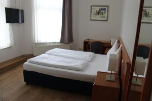 A bed or beds in a room at Stadt-Gut-Hotel Zum Rathaus
