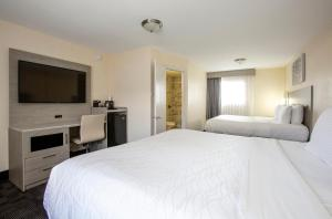 A bed or beds in a room at Hotel Aspen Flagstaff/ Grand Canyon InnSuites