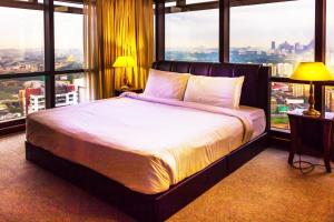 A bed or beds in a room at Eastern Suites @ Times Square KL