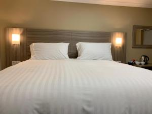 A bed or beds in a room at De Regency Style Hotel