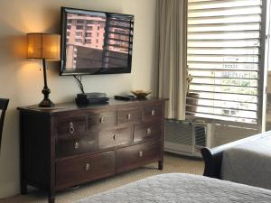 A television and/or entertainment center at Tropical Studios at Marine Surf Waikiki - FREE PARKING - BEST LOCATION - FULL KITCHEN - SWIMMING POOL