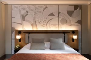 A bed or beds in a room at Hotel La Diligence