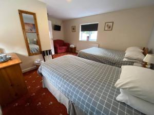 A bed or beds in a room at The Plough Inn Wigston