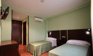 A bed or beds in a room at Hostal Avenida Barajas