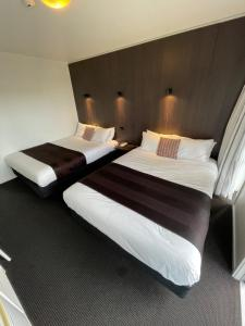 A bed or beds in a room at The Riccarton Hotel