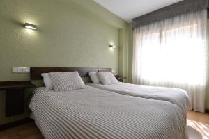 A bed or beds in a room at Hostal Concejo