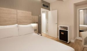 A bed or beds in a room at NH Madrid Chamberí