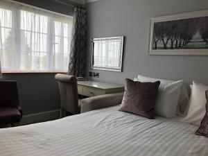 A bed or beds in a room at Exeter Court Hotel