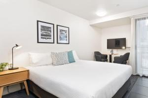 A bed or beds in a room at City Edge North Melbourne Apartment Hotel