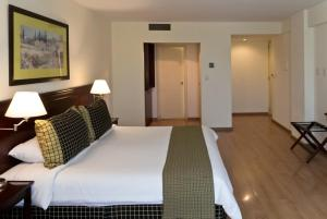 A bed or beds in a room at Amérian Executive Hotel Mendoza