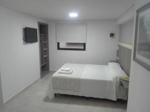 Una cama o camas en una habitación de Hotel Americano Pergamino