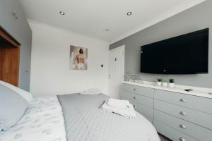 A bed or beds in a room at Beach House With Hot Tub 5 Seat Cinema Private Parking Ultra Modern Property