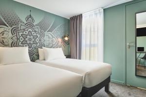A bed or beds in a room at Ibis Styles Paris Gare de l'Est Magenta