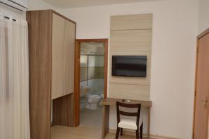 Uma TV ou centro de entretenimento em Sky Ville Hotel Gramado