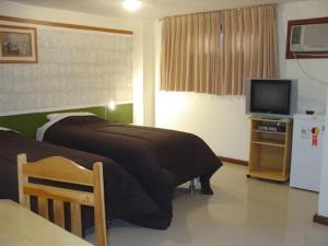 A bed or beds in a room at Quarto Por Dia