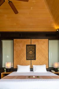 A bed or beds in a room at Baan Krating Phuket Resort