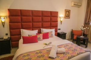A bed or beds in a room at Hotel La Perle du Sud