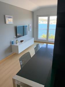 Una televisión o centro de entretenimiento en Apartamento Praia de Quenxe